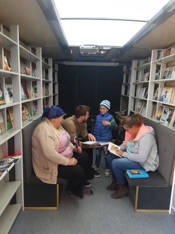 Moldova: Visitors take a look at books inside Bus4Life during an outreach in Northern Moldova. More Info