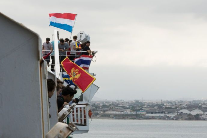 Ecuador: Manta, Ecuador :: Crewmembers wave their flags on deck during the arrival of Logos Hope in port. More Info