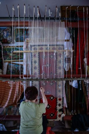 Albania: A woman makes and sells traditional Albanian rugs by weaving numerous threads together on a loom.  Photo by Garrett N More Info