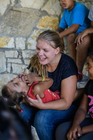 Albania: Women, as part of mercy ministry, pass out backpacks filled with school supplies and clothes to Roma children.  Photo by Garrett N More Info