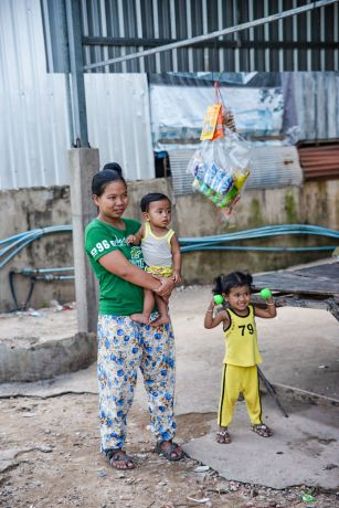 Cambodia: Mother and her two children outside their home. More Info