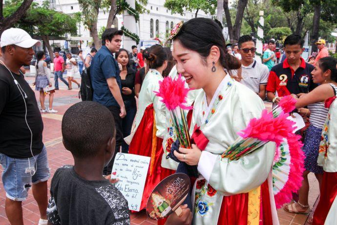 Ecuador: Guayaquil, Ecuador :: Cindy Kim (South Korea) gives a handwritten Bible verse to a young boy. More Info