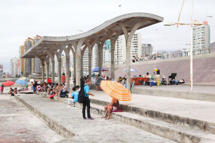 Chile: Antofagasta, Chile :: Travis Beene (Guatemala) gives out flyers promoting Logos Hope to families on the beach. More Info