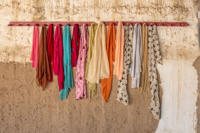 Africa: Head scarves hang on a row of pegs. Photo by Rebecca Rempel More Info