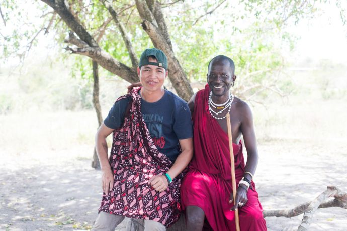 Tanzania: Agustinus (Indonesia) tries on traditional maasai clothing with a chief in a Tanzanian village. Photo by Rebecca Rempel. More Info