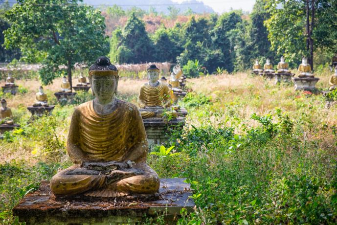 Myanmar: Buddhist Statues Stand in Line Below a Mountain Temple. In total they number in the thousands and you must pass through them to reach the path up the mountain. More Info