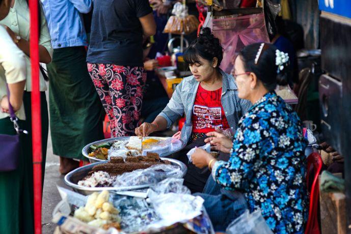 Myanmar: Two women in selling food on a busy sidewalk in Yangon. More Info
