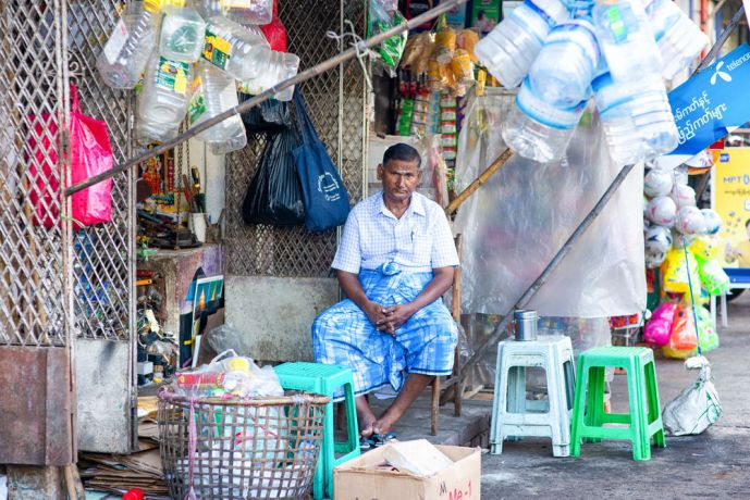 Myanmar: A man sitting outside his shop, framed by plastic bottles everywhere. More Info
