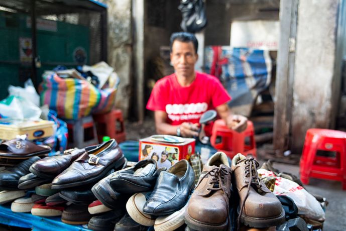Myanmar: A cobbler, or shoemaker, sitting at his outdoor workstation and shop repairing and selling shoes. More Info