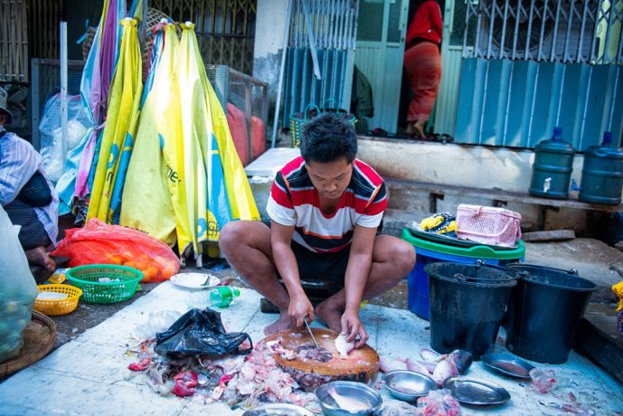 Myanmar: Man prepares fish during market as he prepares to sell them. The nearby river has made fish a common and relatively cheap food choice. More Info