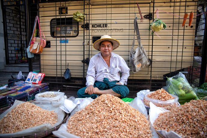 Myanmar: This man is selling a variety of things at market. The rice is often mixed with bugs for extra crunch. More Info