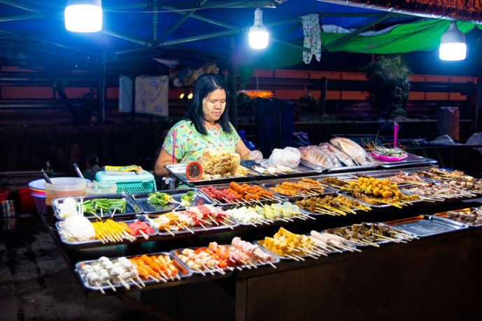 Myanmar: This woman was preparing food for customers at her night market stall. Satay is very popular in the area and very delicious. More Info