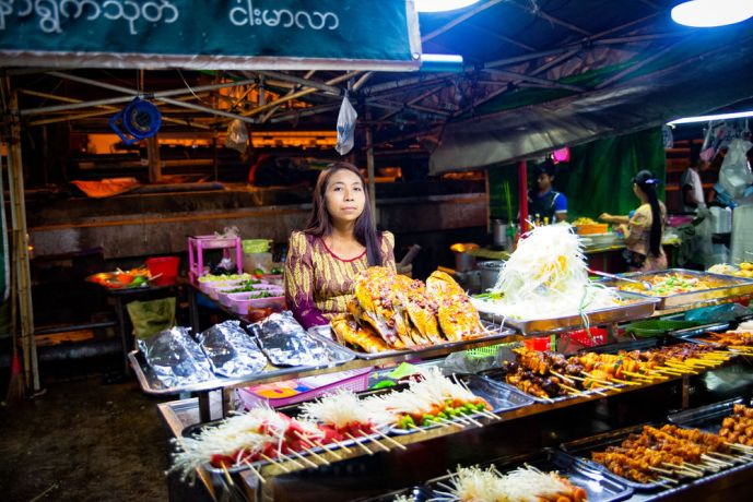 Myanmar: Woman waiting for customers at her night market stall. Satay is very popular in the area and very delicious. More Info