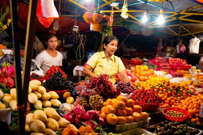 Myanmar: A woman is selling fruit from her stand at a night market. More Info