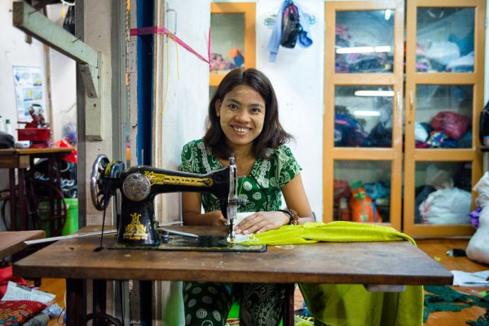 Myanmar: A Seamstress in front of her market store sewing womens clothing. More Info