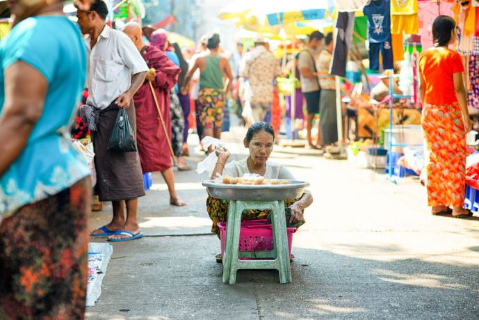 Myanmar: An older woman selling ee jaw kway, a popular dough stick which is dipped into myanmar tea and then eaten. More Info