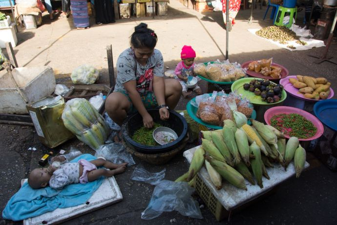 Thailand: A mother works in a local wet market that has fresh vegetables, fruits, fish, and meat for sale by local farmers. The womans two children sit and lie near her while she prepares chilies for sale. - Photo by Ellyn Schellenberg More Info