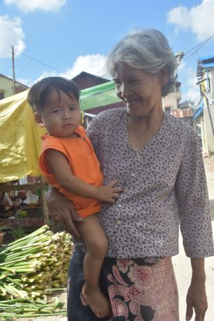 Cambodia: A grandmother walks with her grandson on her hip through a local market in a slum in Phnom Penh, Cambodia. More Info