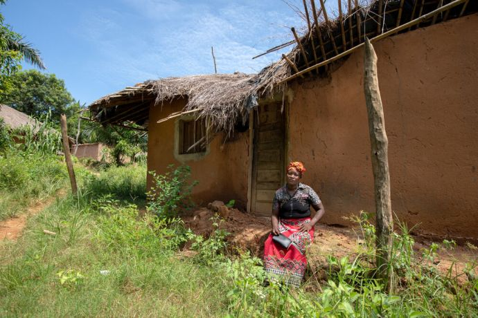 Mozambique: The village Secretary sits in front of a home in her village that was damaged by the heavy rain and winds of Cyclone Idai. Since the disaster, many people have relocated elsewhere. Photo by Rebecca Rempel More Info