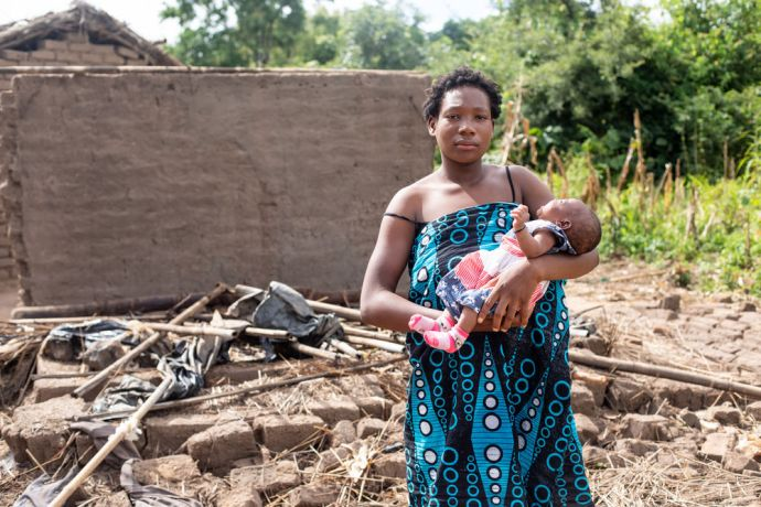 Malawi: Christina stands with her daughter in front of the rubble that used to be her house in a village in Malawi. She lives on the same property as her mother and two of her sisters. In one night, Christina's house—as well as her sisters'—collapsed from the strong rain and winds of Cyclone Idai. They all moved into their mother's house which also suffered damage and now has cracks in the walls and foundation. Photo by Rebecca Rempel More Info