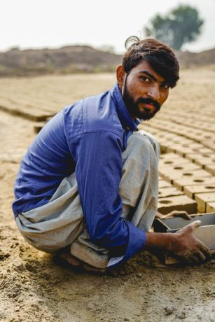 Pakistan: A brick kiln worker laying brick More Info