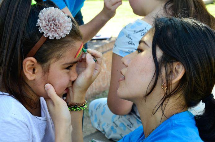 Uruguay: Montevideo, Uruguay :: Sasha Lau (Hong Kong) paints a childs face. More Info