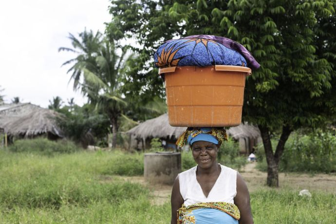 Mozambique: Woman carrying a bucket on her head as she walks in Mozambique. Photo by Rebecca Rempel More Info