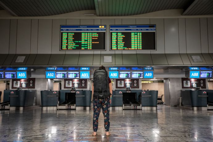 South Africa: A woman stands with her backpack looking at the departure board at an airport. Photo by Rebecca Rempel More Info