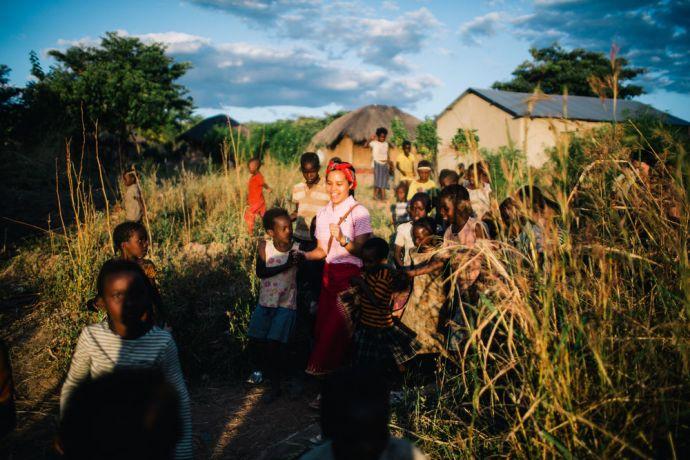 Zambia: Ivy Chiu (Taiwan) walking with local village children in Mpulungu, Zambia. Photo by Doseong Park More Info