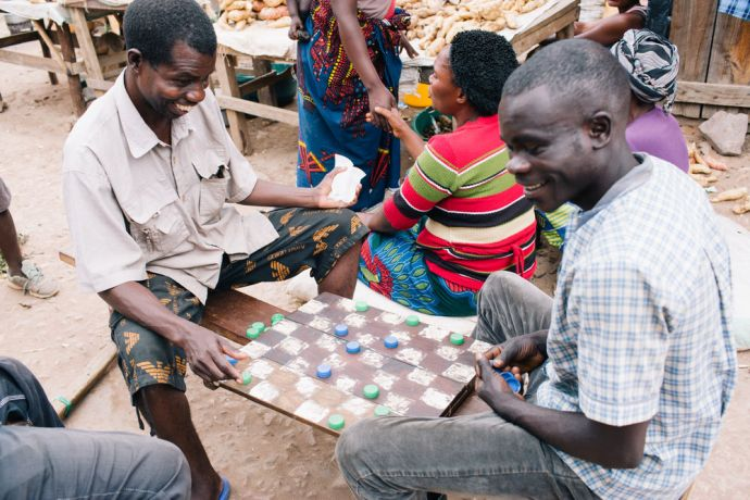 Zambia: Next to the market, local people play a board game. Mpulungu, Zambia. Photo by Doseong Park More Info