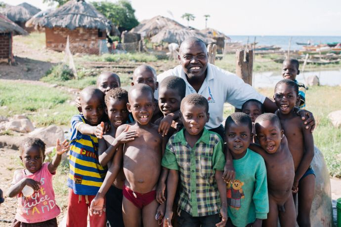 Zambia: Christopher Kasale with local children at the lakeshore in Kapembwa, Zambia.Photo by Doseong Park More Info