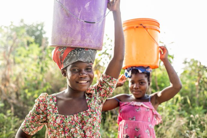 Mozambique: Two girls balance water buckets on their heads as they walk in Mozambique. Photo by Rebecca Rempel. More Info