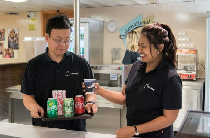 Uruguay: Montevideo, Uruguay :: Sarah Sookchan (Trinidad and Tobago) and PK Kamalatilaka (Thailand) serve drinks in the refurbished café on board. More Info