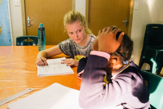 South Africa: An OMer is helping a school kid with homework at the After School Programme at AIDS Hope South Africa. More Info
