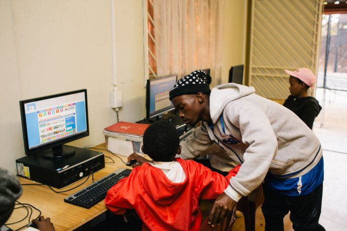 South Africa: A local volunteer is helping schoolchildren with computer literacy at the After School Programme at AIDS Hope South Africa. More Info