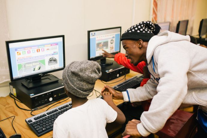 South Africa: A local volunteer is helping children with computer literacy at the After School Programme at AIDS Hope South Africa. More Info