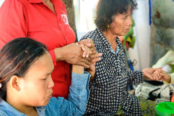 Cambodia: Holding hands to pray during a Bible study in a poor part of Phnom Penh. More Info