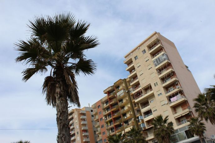 Albania: Many-storied apartment buildings and palm trees in the busy port city of Durrës, Albania. More Info