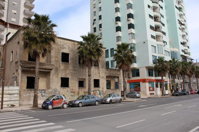 Albania: A new apartment building offset by palm trees and a neglected, Communist-Era looking building in the busy port city of Durrës, Albania. More Info
