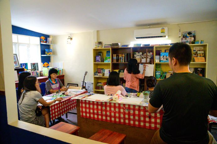 South East Asia: Ailani teaching a painting class at a cafe. More Info