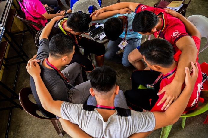 Malaysia: A group of guys praying before teens start to arrive at TeenStreet KK. More Info