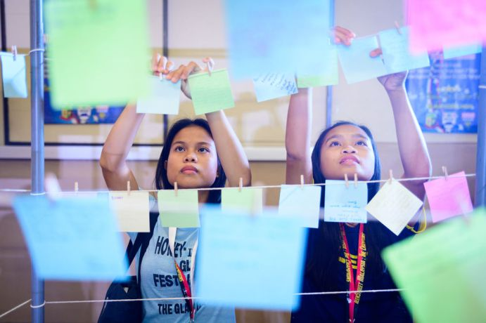 Malaysia: Two girls hanging a post it note with what they are thankful for. More Info