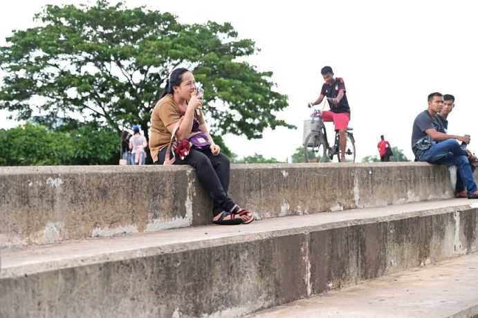 Laos: A woman enjoying dinner in the park. More Info