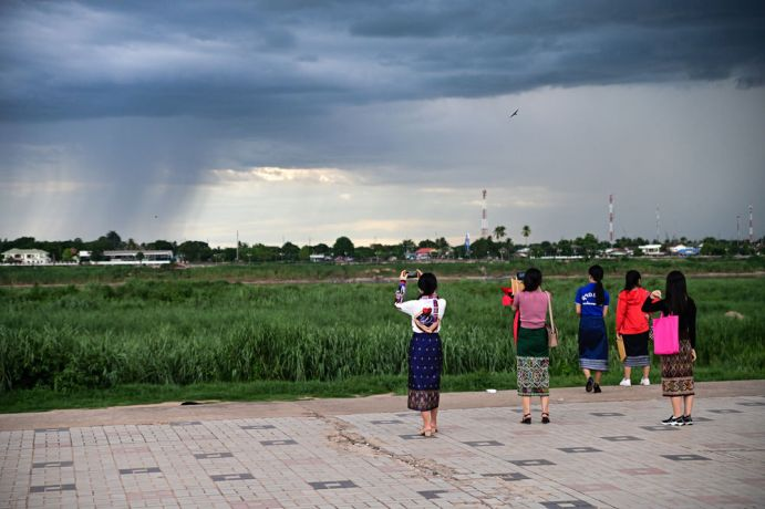 Laos: People at the park watching the thunderclouds roll in. More Info