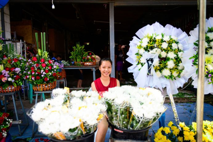 Laos: A young woman sells flowers outside of a Bhuddist temple. More Info