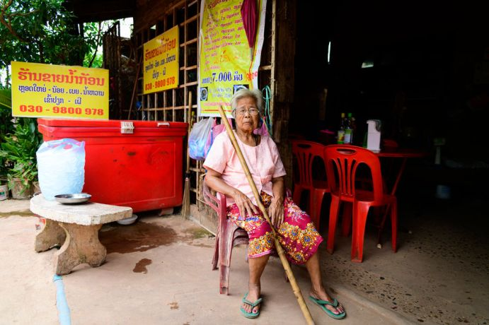 Laos: A woman sits outside her small store. More Info