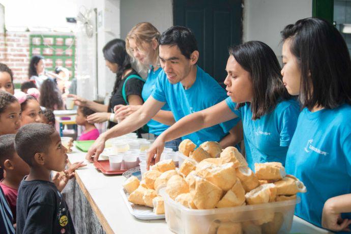 Brazil: Santos, Brazil :: Gracia Lee (Hong Kong), Mima Bessa (Brazil), Aman Hassan (Indonesia) and Evelina Carlsson (Sweden) help to feed children from a an underprivileged neighbourhood . More Info