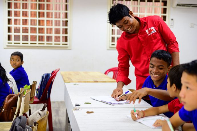 Cambodia: A school run by the team in Cambodia, this class is taking place in the new school building built from shipping containers. More Info
