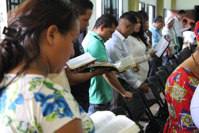 El Salvador: Brothers and Sister from a local Church reading Matthew 28:19 More Info
