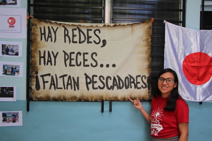 El Salvador: An OM staff member standing next to a sign during a Church mobilization, ponting the quote that says... There are fishing rods, there are fishes, but fishers are missing. More Info